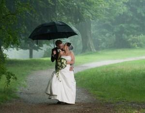 Brudepar i skybrud midt i bryllupsfotograferingen