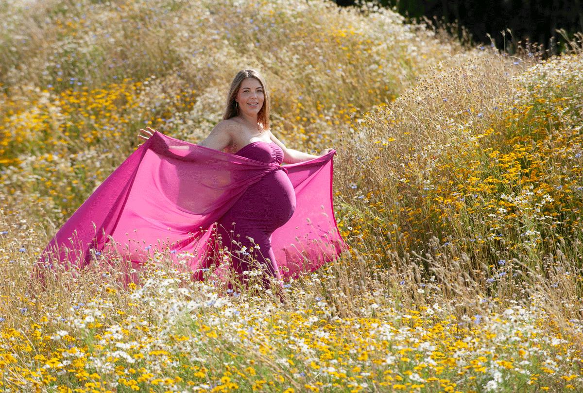 Gravid pige fotograferet i rundkørsel med tre høje i Humlebæk med et flot blomsterhav af markblomster som Fredensborg Kommune har plantet for at øge biodiversiteten. Fotograf Peter Dahlerup fra Fredensborg i Nordsjælland