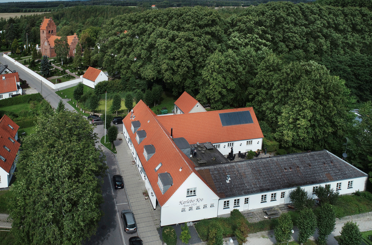 Corona fri optagelse fra en drone af Karlebo Kro i forgrunden med Karlebo Kirke bagerst - dronefoto i samarbejde med Fredensborg Drone Service og redigeret af fotograf Peter Dahlerup